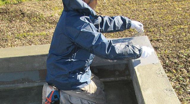 立上り部や床面に、防水材を塗布しながら、補強布を張っていきます